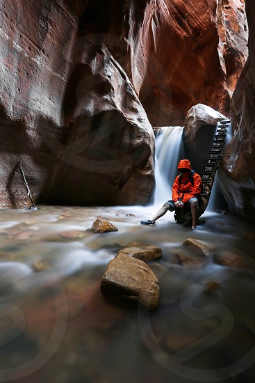person in orange hoodie sitting in red rock cave photo