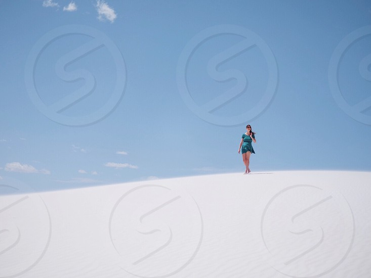 woman in blue dress standing on desert photo