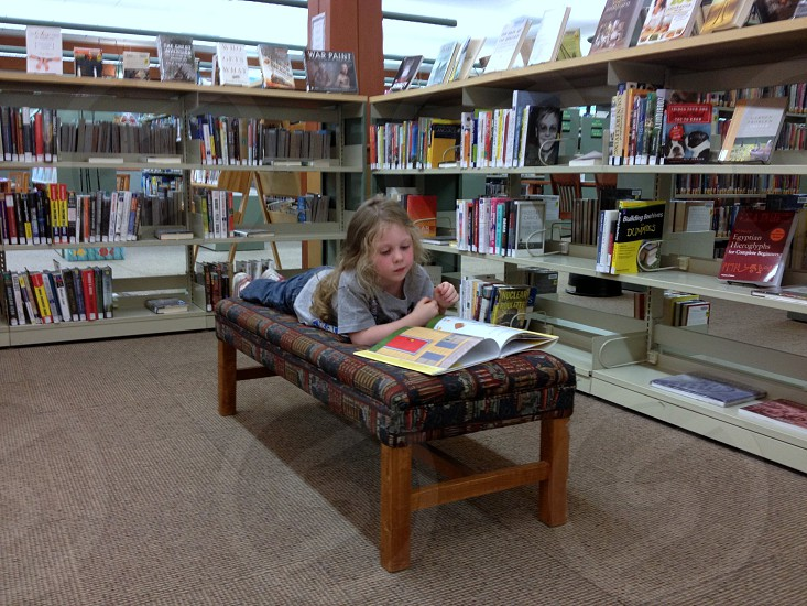 Four year old girl reading books in library photo