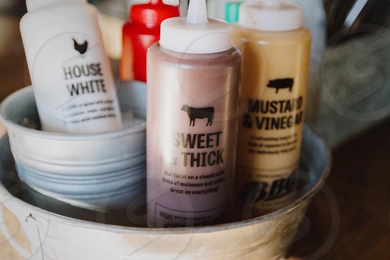sweet & thick bottle beside mustard & vinegar bottle in white bucket photo