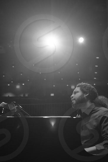 grayscale photo of man in dress shirt playing piano photo