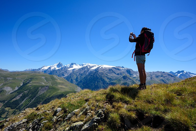 Woman trekker taking a picture of the mountain landscape in the French Alps France photo