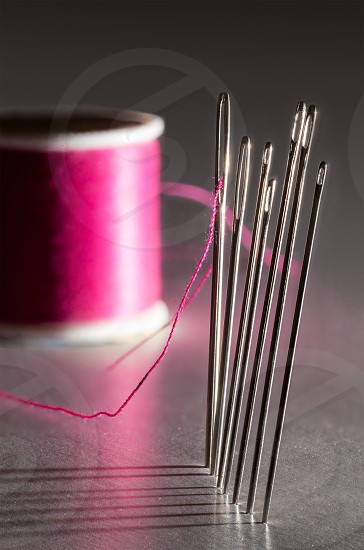 Row of sewing embroidery needles with red thread and shadows with bobbin photo