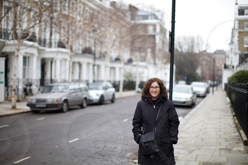 woman in black coat with cross body bag on the street photo
