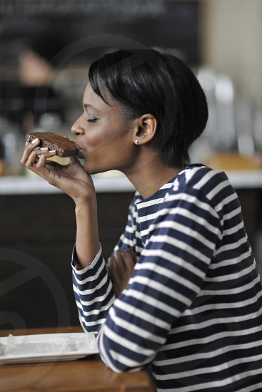 woman in black and white stripe long sleeve shirt eating chocolate cake photo
