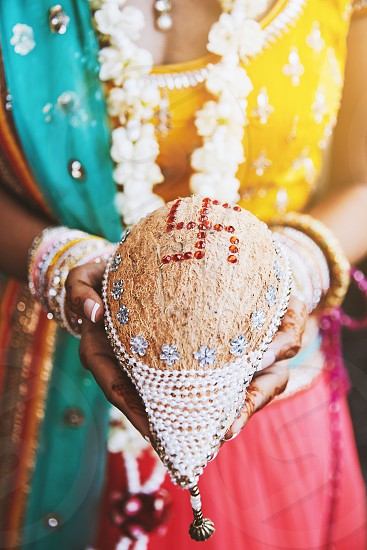 Indian bride hand with mehndi (henna tattoo) with bunch of bracelets or bangles on her wrist holding the coconut shagun nariyal the item for prayer ceremony of indian marriage ritual photo