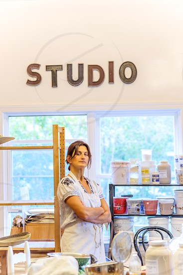 woman in white apron standing beside jars and buckets on shelf under studio signage on wall photo