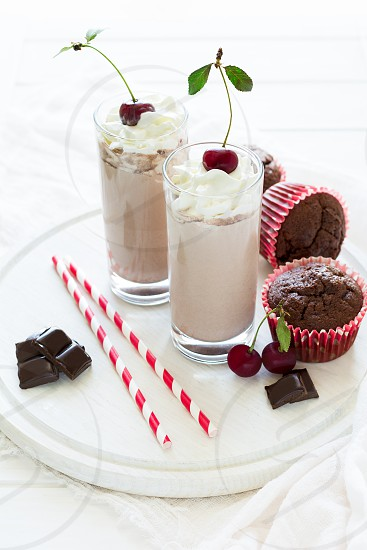 Two glasses with milkshakes on white wooden background. Selective focus photo