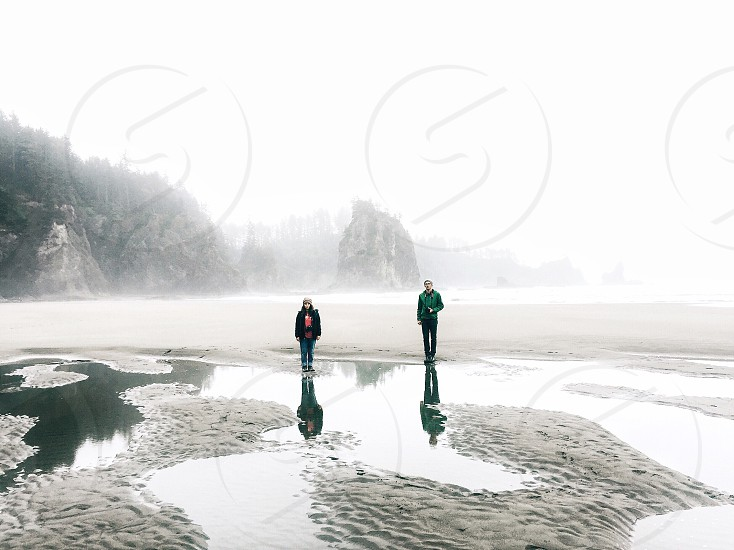 two people walking on white sand with body of water during daytime photo