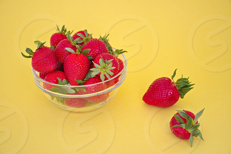 Strawberries in the transparent bowl on the yellow background photo