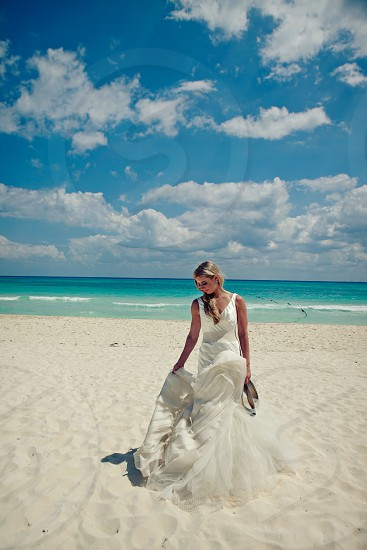 bride holding her shoes standing on the beach photo