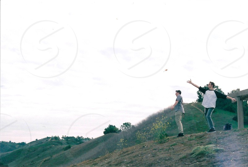two men on cliff looking out in khakis jeans and one man with arm up throwing rock photo