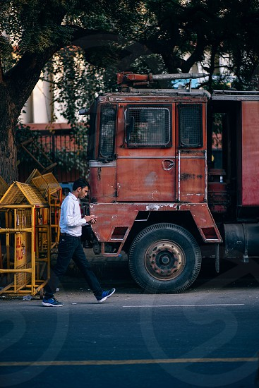 Young Indian man texting on his smartphone while walking photo