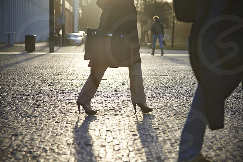 Close up of people's legs in business attire walking on cobble stones in a modern financial business district during sunrise photo