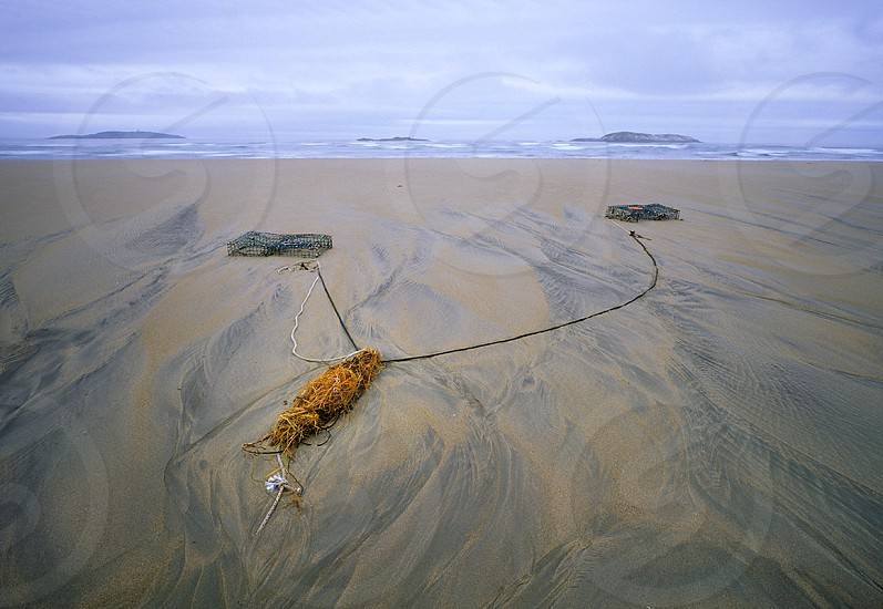 2 lobster traps half buried in the sand after a storm on the rarely sandy coast of Maine. photo