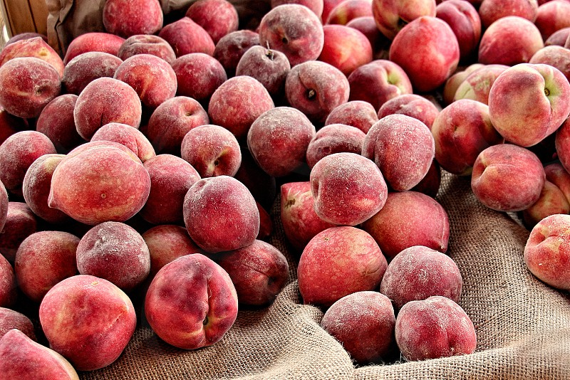A pile of fresh peaches are spilled out onto a burlap cloth photo