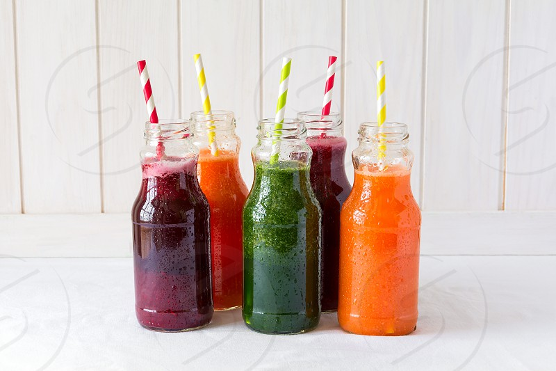 Detox drinks in bottles: fresh smoothies from vegetables: beet carrot spinach cucumber and apple on white background photo