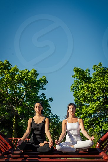 two relaxed young beautiful women meditating wearing black and white clothes outdoors with blue sky and green vegetation photo
