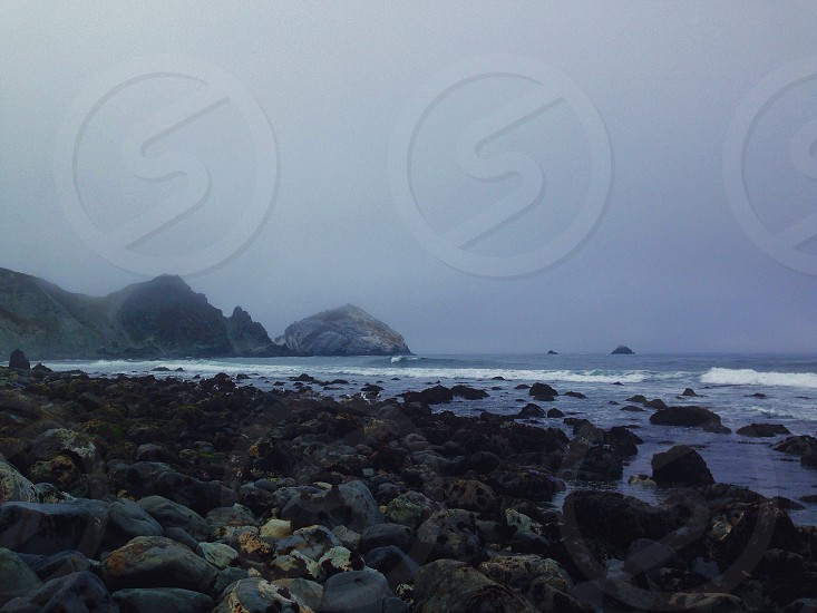 view of black rock fragments and ocean photo