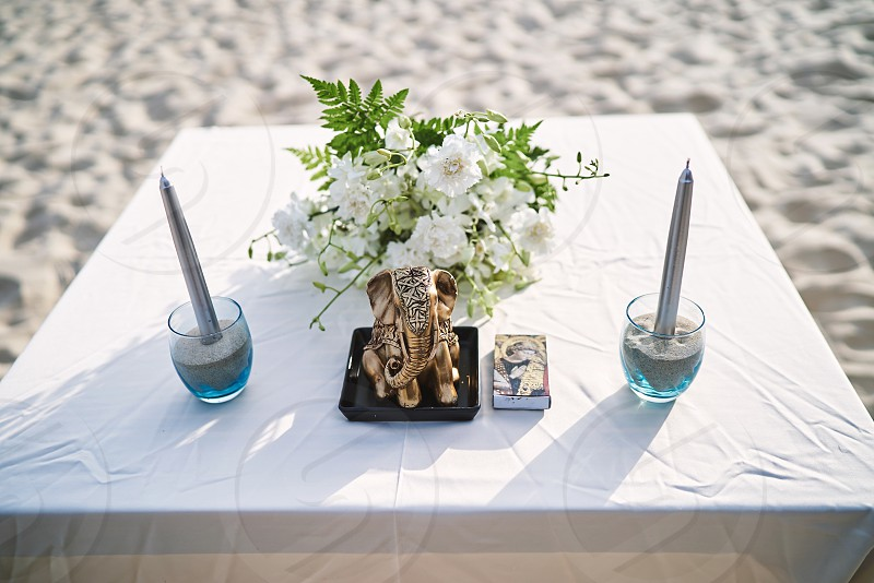 Altar with white tablecloth with ganesha statue and silver candle on the sand glass during formal wedding ceremony on the beach photo
