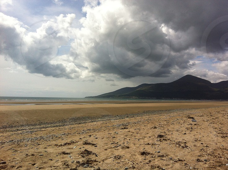landscape photography of mountain in front of seashore under cumulus clouds photo