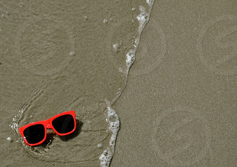 Sunglasses in the sand and waves photo