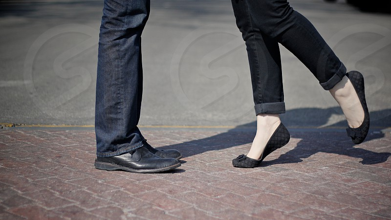 A couple's feet on brick street photo