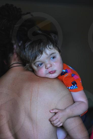 person holding child in orange shirt photo