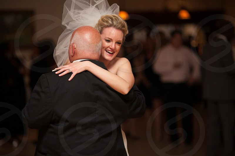 bride dancing with a man in black suit photo