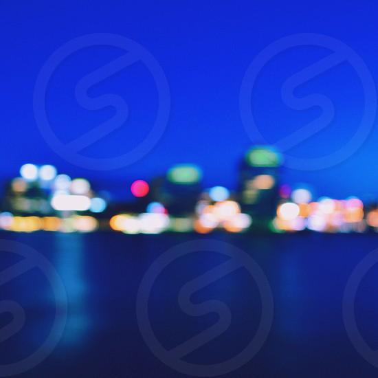 bokeh photo of skyscraper near water below blue sky during nighttime photo