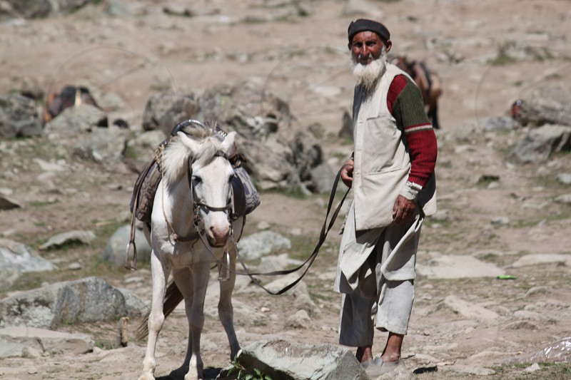 This old man with his horse earns merely 5 $ a day by carrying tourist on the back of the horse to the hilly areas of sonamarg in the Kashmir region. photo