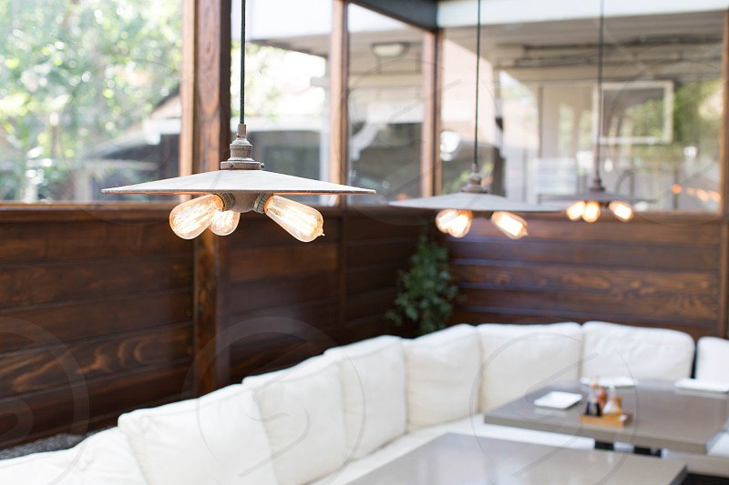 selective focus photography of interior view photo of restaurant white padded sofa and tables during daytime photo