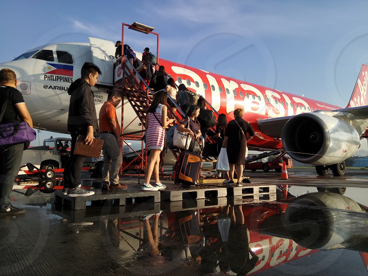 crowd of people entering Airasia plane during daytime photo