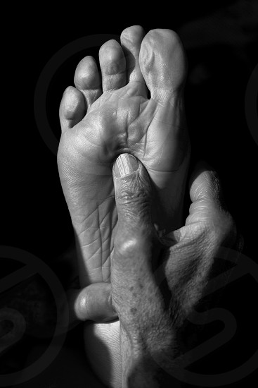 senior hands doing foot reflexology photo