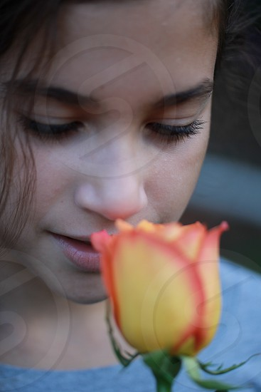 woman in gray shirt in front of yellow and pink flower in macro lens photo