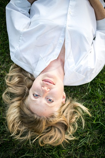 A young woman laying on her back in the grass upside down with a slight smile while looking at the camera. Blouse hair pearl earrings Caucasian girl lady relaxed comfortable natural honest home blue ground white. photo