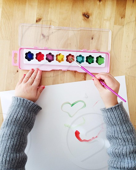 human arms with paint brush paper with painted heart and paint tray photo