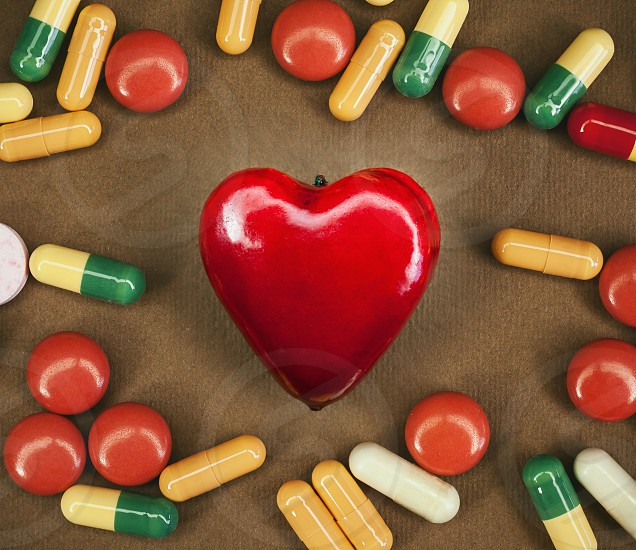 Conceptual composition about heart sickness various colorful pills around souvenir in shape of heart as symbol.  photo