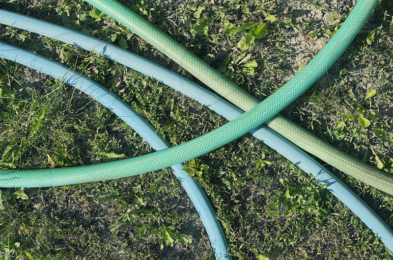 above abstract blue closeup color crossing detail equipment garden gardening grass green hose irrigate irrigation lawn lines nature nobody object outdoor outdoors outside pipe plastic pvc rubber summer tool tube vertical yard  photo