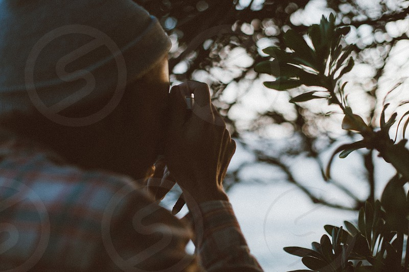 person wearing white knit cap using camera taking photo photo