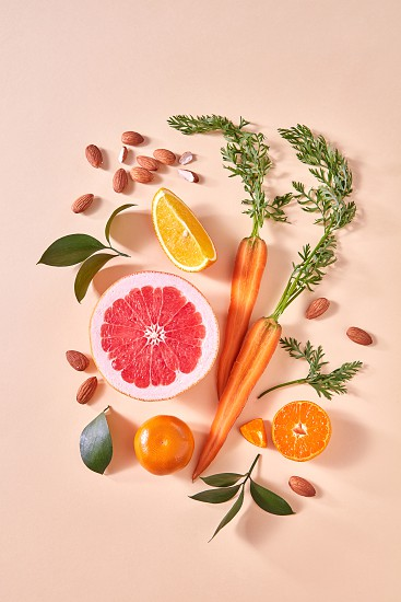 Carrot slices of orange and grapefruit almond mandarins green leaf - on a paper background. Concept of colorful organic food. Flat lay photo