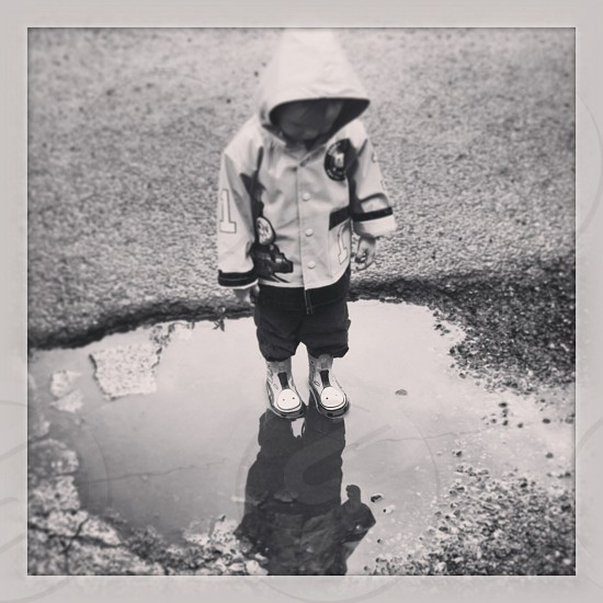 Little boy looks at reflection in puddle photo