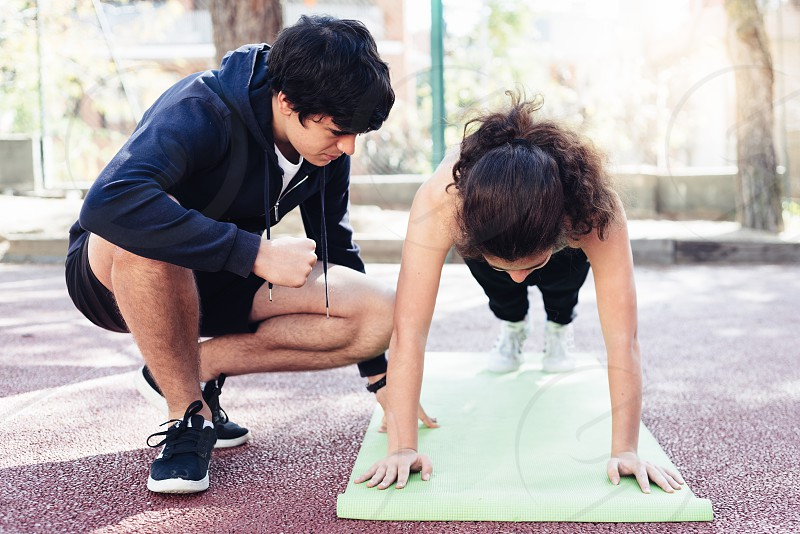 Girl doing planks while a young personal trainer is encouraging her photo