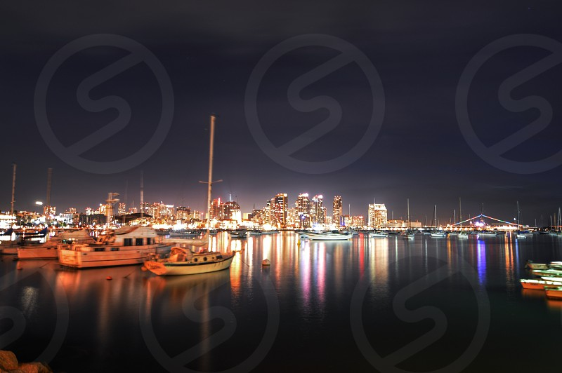 view of yachts by the city at night photo