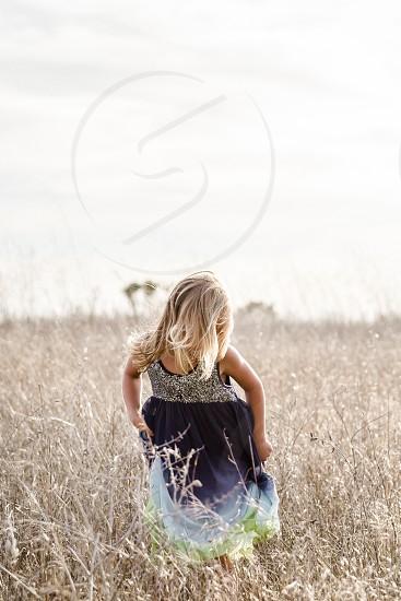 child girl dress flown sequins hair wind breeze soft light field dead field brown grasses vertical landscape center-weighted tan blue photo