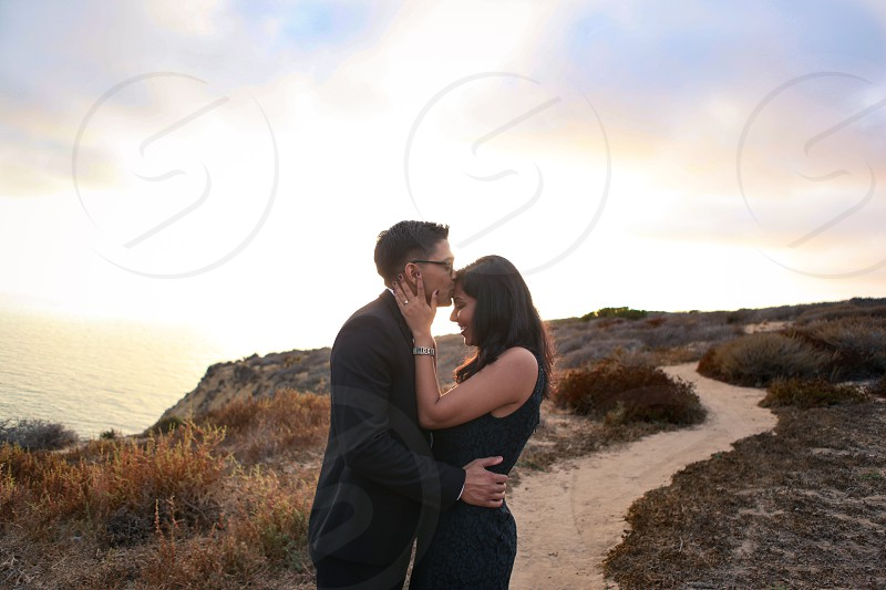 man in black suit kissing woman's forehead in black sleeveless dress in behind of lake photo