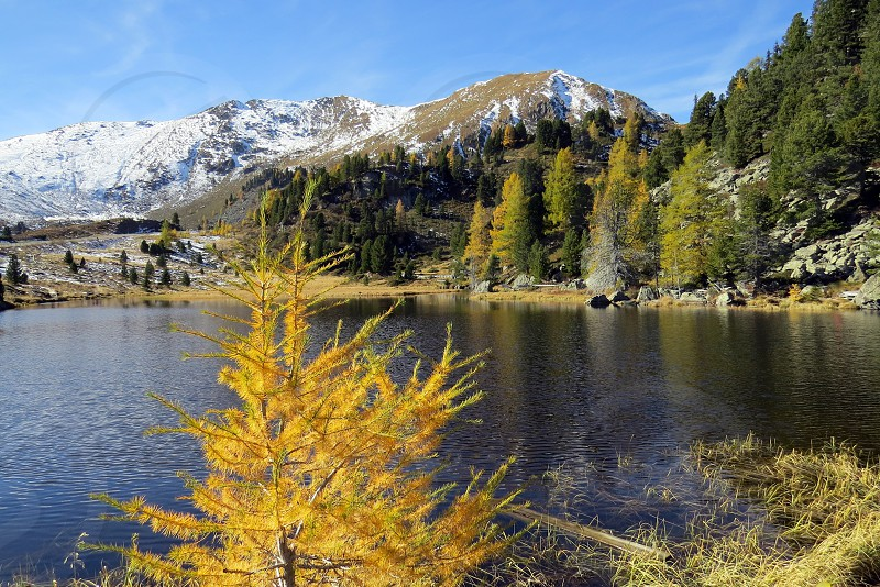 Nockberge National Park in Austria            Austria Nockberge lake mountains landscape snow panorama view hiking autumn fall nature outdoors outside sky blue beauty beautiful sunny tree plant larch colorful peak photo