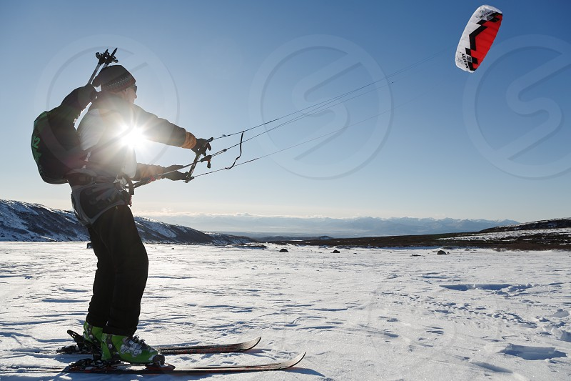 KAMCHATKA PENINSULA RUSSIA - NOVEMBER 22 2014: Snowkiting or kiteboarding - sportsman glides on skis on snow in sunny weather at sunset. photo