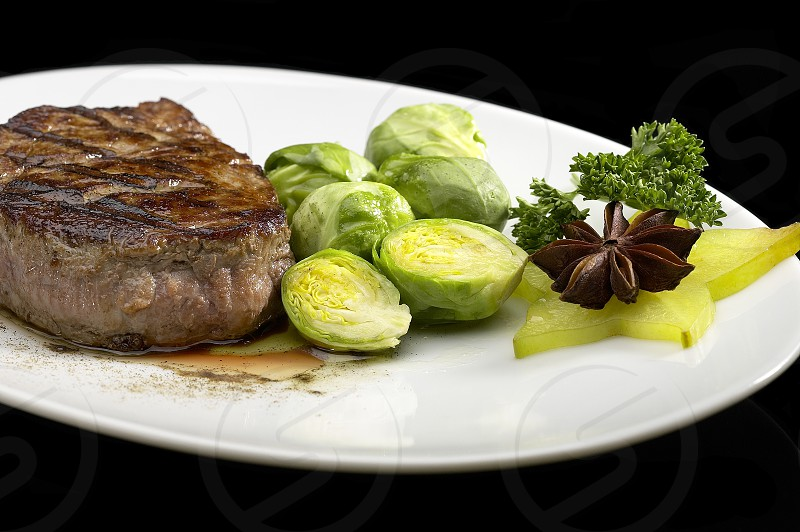 juicy filet mignon on plate with brussel sprout over black background photo