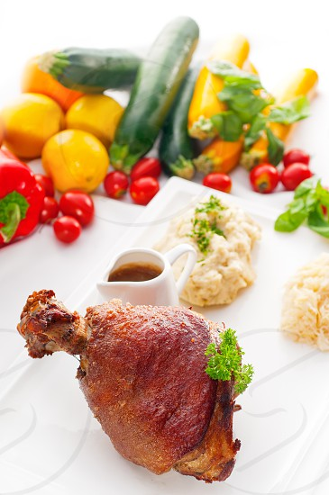 original German BBQ pork  knuckle served with mashed potatoes and  sauerkraut fresh vegetables on backgroundMORE DELICIOUS FOOD ON PORTFOLIO photo